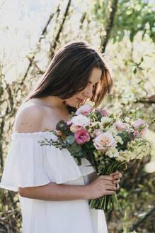 Woman smelling fresh flower bouquet - DSIF00096