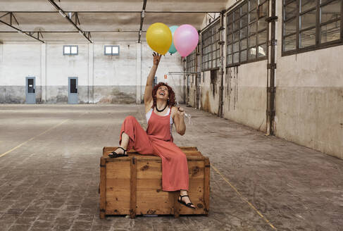 Happy woman playing with colorful balloons while sitting on wooden box - VEGF02788
