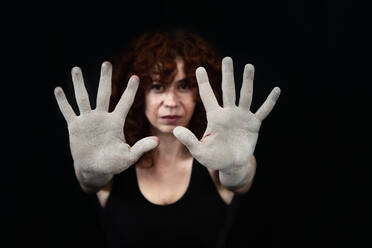 Woman showing hands covered with white dust against black background  - VEGF02794