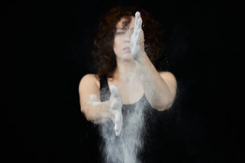 Woman clapping hands covered in white dust against black background - VEGF02797