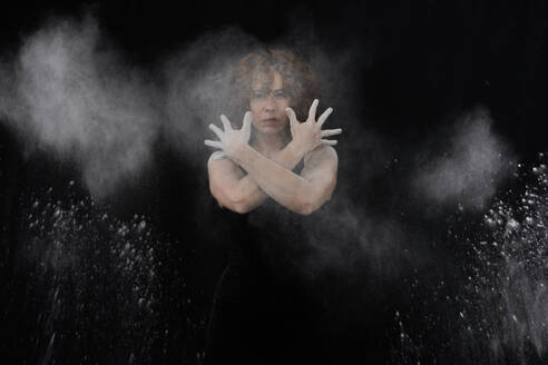 Woman throwing white dust besides herself while standing against black background - VEGF02800