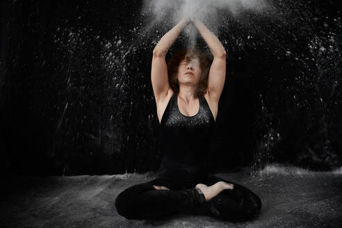 Woman sitting on floor while clapping with white dust over herself against black background - VEGF02806