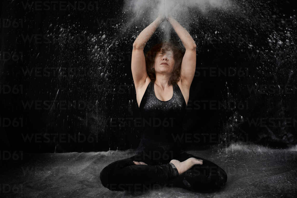 Woman sitting on floor while clapping with white dust over herself against black background - VEGF02806 - Veam/Westend61