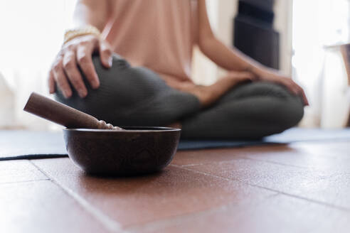 Woman doing yoga at home, singing bowl in the foreground - FMOF01040