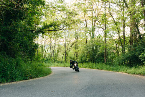 Young male motorcyclist on vintage motorcycle on rural road bend, Florence, Tuscany, Italy - CUF56226