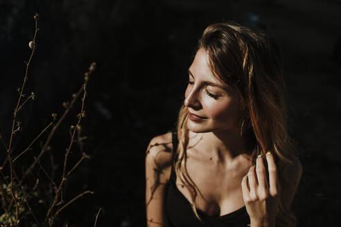 Thoughtful woman standing in sunlight - GMLF00440