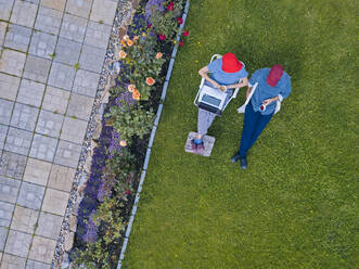 Aerial view of couple sitting in garden - KNTF05259