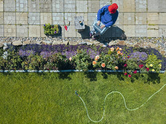 Aerial view of woman sitting on terrace in garden - KNTF05265