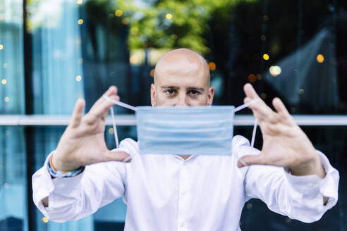 Bald man holding protective face mask while standing outdoors - DGOF01238