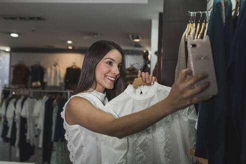 Smiling beautiful woman taking selfie with outfit at store - DSIF00100
