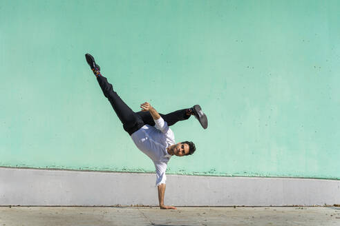 Businessman doing handspring in front of green wall - AFVF06955