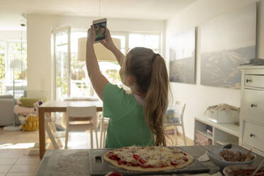 Girl taking selfie with pizza on kitchen island at home - JOSEF01532