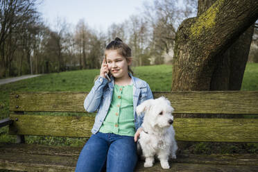 Smiling girl with dog talking on phone over bench in park - JOSEF01538