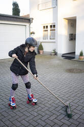 Girl skating while cleaning porch with broom - JOSEF01550