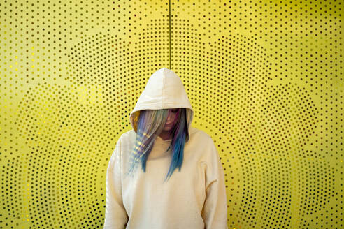 Portrait of young woman with dyed hair in front of yellow wall - VPIF02857