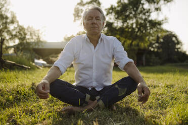 Man practicing yoga while sitting in lotus position at yard - GUSF04363