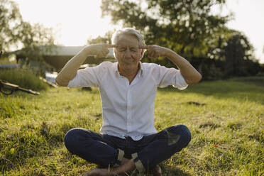 Man with eyes closed practicing yoga while sitting in backyard - GUSF04366
