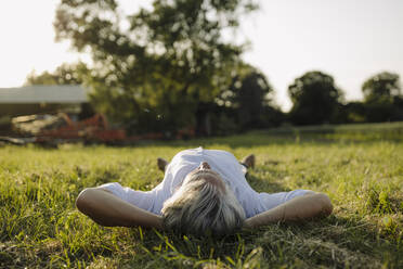 Man with hands behind head lying on grass in yard - GUSF04369