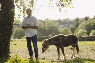 Man with hands clasped standing by goat in field - GUSF04387