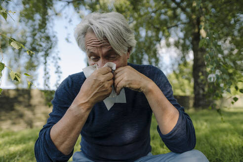 Wrinkled man blowing nose while sitting in field - GUSF04390
