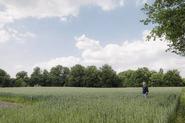 Man with hands in pockets standing in agricultural field - GUSF04429