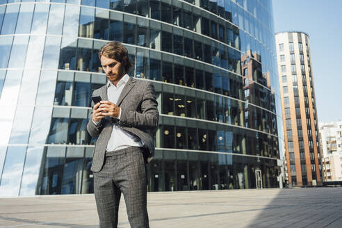 Handsome young businessman using smart phone while standing against modern office building in downtown on sunny day - VPIF02898