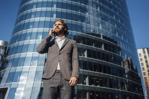 Businessman looking away while talking on mobile phone against modern office building during sunny day - VPIF02901
