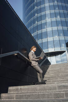 Businessman using laptop while leaning against wall on staircase in downtown during sunny day - VPIF02934