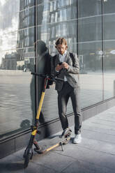 Young male commuter using smart phone while leaning on glass by electric push scooter in financial district - VPIF02955