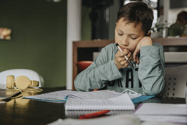 Schoolboy learning at home, head in hands, solving problem - MFF06040