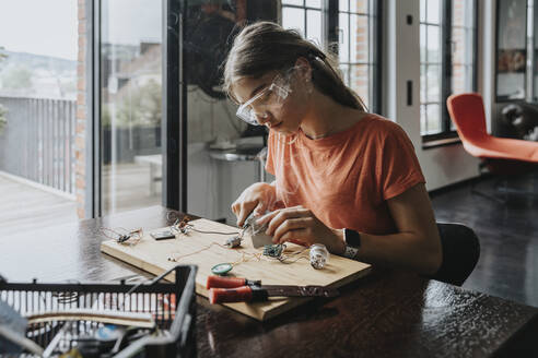 teenage girl tinkering with soldering iron at home - MFF06067