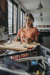 Teenage girl tinkering with soldering iron at home - MFF06070