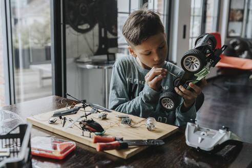 Boy assembling on remote-controlled toy car with screwdriver - MFF06073
