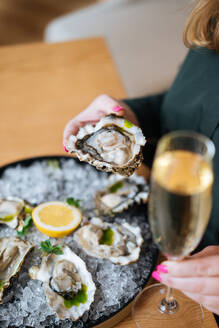 Unrecognizable cropped person with glasses of champagne trying delicious oysters with lemon and herbs in restaurant - ADSF11754