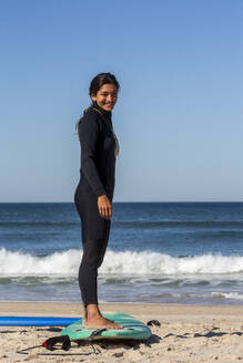 Beautiful young woman smiling while standing on surfboard at beach - NGF00599