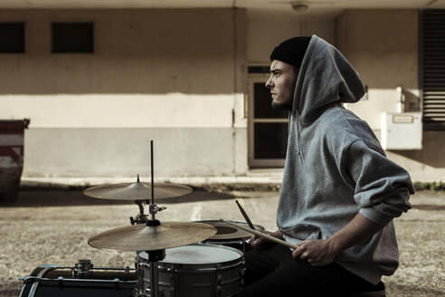 Handsome musician wearing hood playing drums at back yard - SAJF00040