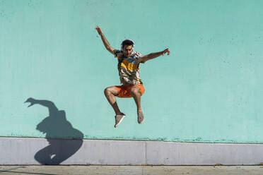 Casual man jumping in front of colorful wall - AFVF06987