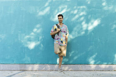 Casual man leaning against blue wall - AFVF07002