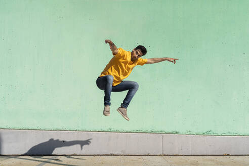 Casual man jumping in front of colorful wall - AFVF07008