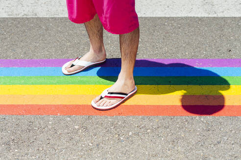 Man standing on rainbow color crosswalk - JCMF01192