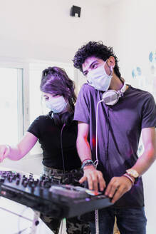 DJing couple wearing face masks while mixing sound at recording studio - MRRF00304