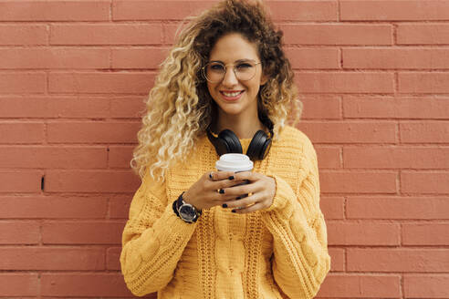 Happy young female student with long curly blond hair holding disposable coffee cup against red brick wall - BOYF01364