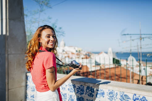Young woman holding camera while standing by retaining wall at Alfama, Lisbon, Portugal - DCRF00662