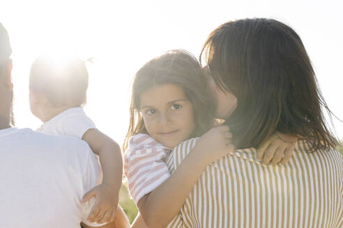 Cute girl embracing mother by father with sister at park during sunset - JCZF00195