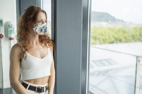 Thoughtful woman wearing protective mask while looking through window - MTBF00609