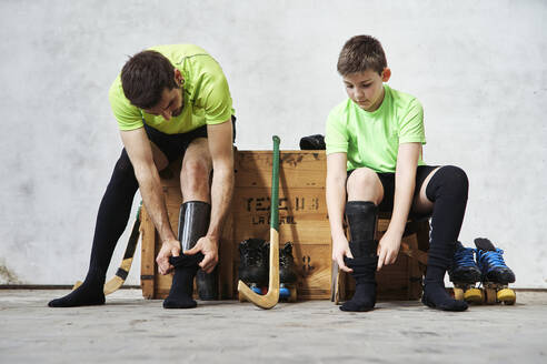 Father and son wearing socks while sitting on wooden box at court - VEGF02809