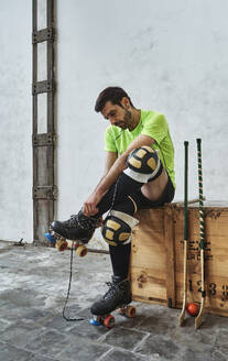 Mature male athlete wearing roller skate while sitting by hockey sticks on wooden box against wall at court - VEGF02821