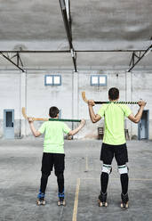 Father and son holding hockey sticks at sports court - VEGF02824