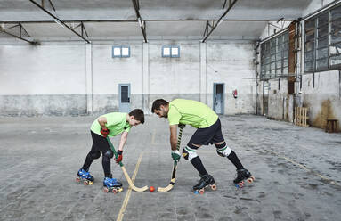 Father and son in face off while playing roller hockey on court - VEGF02827