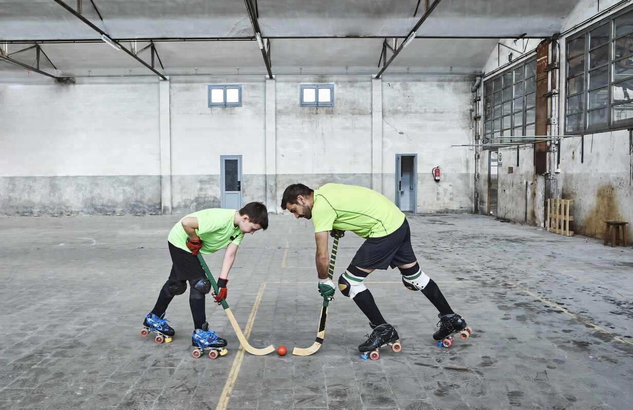 Father and son in face off while playing roller hockey on court - VEGF02827 - Veam/Westend61